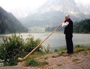 A Swiss playing alphorn near a mountain lake