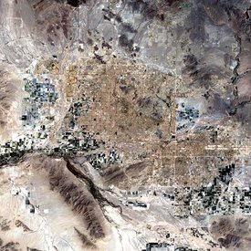 Phoenix is surrounded by twenty two towns and cities that have grown so closely together that it is almost impossible to distinguish one from another in this satellite image. The large cluster of light brown pixels gridded by horizontal and vertical lines (roads and highways) demarcates the Greater Phoenix urban area.