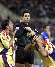 A football (soccer) player is cautioned by a referee